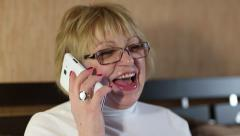 Senior woman in glasses with smartphone speaks smiling, laughs and gesticulates Stock Footage