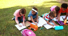 School children doing homework on grass Stock Footage