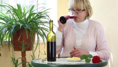 Senior woman sits at a table, drinking wine and eating cheese Stock Footage