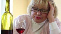 Depressed senior woman sitting and looking at a bottle of wine Stock Footage