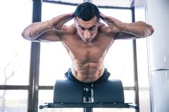 Muscular man flexing back muscles on bench - stock photo