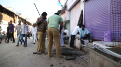 Men opening sewerage at a street in Mumbai. Stock Footage