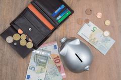 Buisness, banking and savings concept -   money into small grey piggy bank Stock Photos