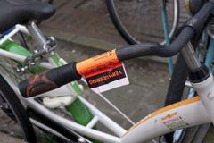 Cycling inconvenience, remove sticker on bike in downtown Amsterdam Stock Photos