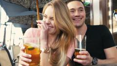 Attractive couple being silly at cafe with beer on vacation - stock footage