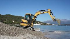 Excavator working on the beach Stock Footage