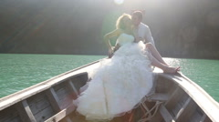 Groom embraces bride sitting in longtail boat Stock Footage