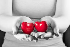 Stock Photo of Two hearts in woman hands. Love, care, health, protection.