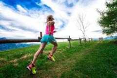 Blonde girl athlete runs a mountain path in the green grass Stock Photos