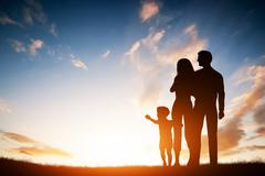 Happy family together, parents with their little child at sunset. - stock illustration