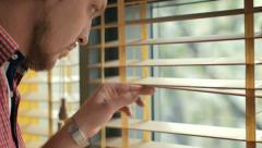 Attractive man looking through the blinds of the window to the street Stock Footage