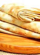 Stock Photo of Lavash, tortilla wrap Bread on the cutting board on white