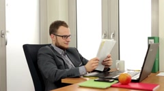Men sitting behind the desk and in the same time he is  reading notes. (44) - stock footage