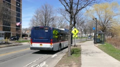 Bus leaving   college town Stock Footage