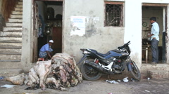 Animal skin on pile and motorcycle in front of a house in Mumbai. - stock footage