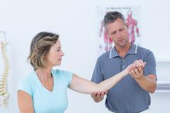Doctor stretching his patients arm Stock Photos