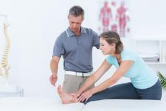 Physiotherapist helping his patient stretching Stock Photos
