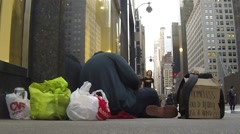 Stock Video Footage of Homeless man sits on streets of New York as people walk by