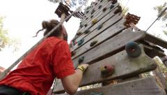 MOSCOW. CICRA 2014: Young man climbs on the climbing wall in the adventure park Stock Footage