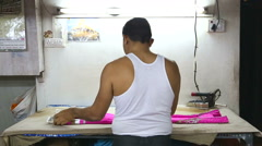Man folding clothes in a workshop in Mumbai. Stock Footage