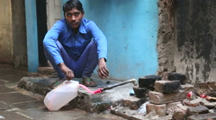 Portrait of Indian man filling container with water on the street. - stock footage