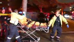 Paramedics transporting unconscious patient on stretcher and into ambulance Stock Footage