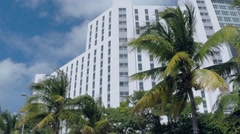 Wide angle master shot of exterior of multi-story white building with many wi Stock Footage