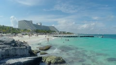 Tourists play in sea and on beach in front of beautiful Cancun resort Stock Footage