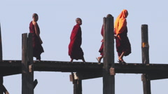 Young monks from local monastery in traditional buddhist red clothes on U Bein Stock Footage