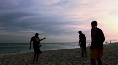 Boys playing soccer on the beach - stock footage