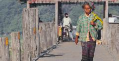 Woman in traditional costume crossing U Bein bridge at day Stock Footage