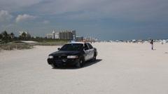 Police Car with Flashing Lights and Beachgoers on Miami Beach Stock Footage