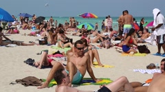 A Group of Male/Female Sunbathers on the Beach - stock footage