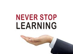 Never stop learning words holding by businessman's hand Stock Photos