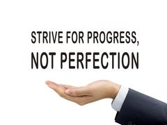 strive for progress not perfection holding by businessman's hand - stock photo
