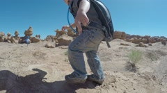 Boy in goblin valley state park with hydration pack Stock Footage