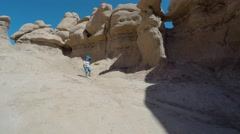 Boy running around in goblin valley state park rock formations Stock Footage