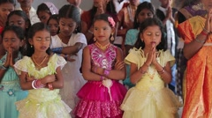 Little girls in pink and yellow dresses praying in India - stock footage