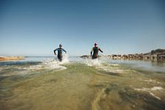Two triathletes rushing into water for swim portion of race - stock photo