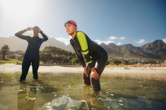 Determined athletes in wet suits preparing for triathlon Kuvituskuvat