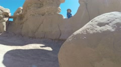 Boy sitting in goblin valley state park rock formation Stock Footage