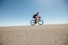 Female cyclist on a country road training for triathlon - stock photo