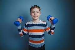 Teenager boy brown European appearance holds a blue dumbbell on Stock Photos