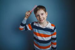 teenager boy of about ten European appearance brown hair combs h - stock photo