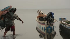 Man carrying fish nets to a boat in Sri Lanka Stock Footage