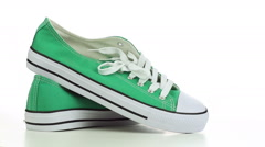 Green sneakers revolve on a white background Stock Footage