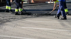 Workers paving a road in detail Stock Footage