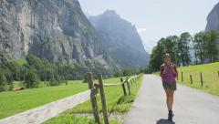 Woman hiking in Switzerland Swiss alps landscape -  Female hiker tourist on hike Stock Footage