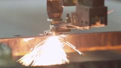 A laser in a factory cuts through metal, creating sparks Stock Footage