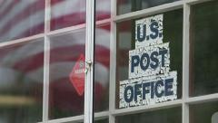 Small post office with flag reflected in window Stock Footage